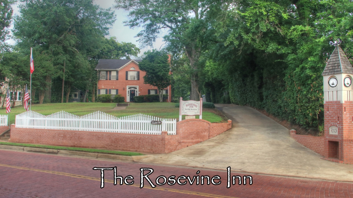 The Exterior of The Rosevine Inn Bed & Breakfast featuring a brick building, white picket fence and brick clock tower