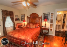 The Churchill Room with a red and gold bedspread, wood headboard and wood floors