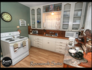 Roosevelt Kitchen with a white 4 burner electric stove and oven and white built in cabinets