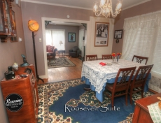 Dining Room in the Roosevelt with a wood table and four chairs, a blue rug and a decorative chest