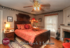 The Sherlock Bedroom featuring a red bedspread with highback wood headboard, wood floors, a wood burning fireplace and ceiling fan