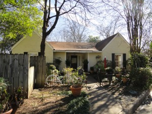 The exterior of 428 Sunny Lane in Tyler Texas. Light yellow/beige brick with brown composition roof. Small metal fence with decorative white bicycle and small outdoor garden in the front