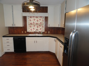 Kitchen at 428 Sunny Lane with White Cabinets, stainless steel refrigerator, black disasher and wood backspash