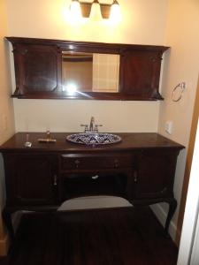 Dark wood bathroom sink with dark wood cabinets at 428 Sunny Lane